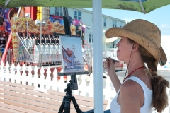 "Maggii Sarfarty of Easton, Md. paints on the Ocean City Boardwalk during the ""Artists Paint OC"" plein air event in August."